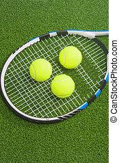 Tennis concept: racket with balls lies on green grass court