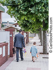 Father and little son walking on the street to the school -...