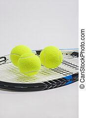 Tennis racket and three green balls on white background