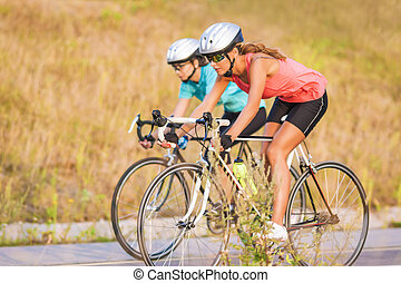 Two women exercising on bicycles outdoors. horizontal image...