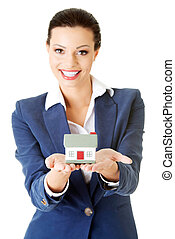 Businesswoman holding house model - real estate loan concept