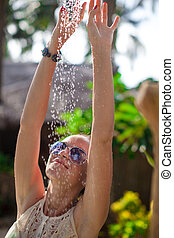 Young woman in tropical shower on exotic resort