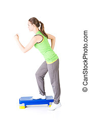 Fitness girl is working out with stepper , isolated on white...
