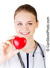 Female doctor holding red heart in hand.