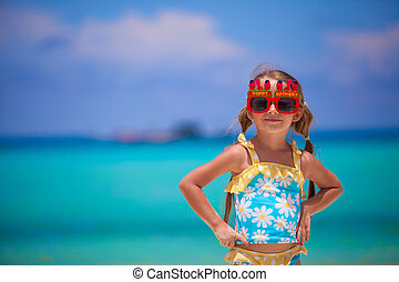 Adorable little girl in Happy Birthday glasses smiling and having fun at white beach