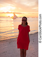 Silhouette of young beautiful woman at tropical beach in sunset