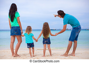 Back view of young family with two daughters at exotic beach on sunny day