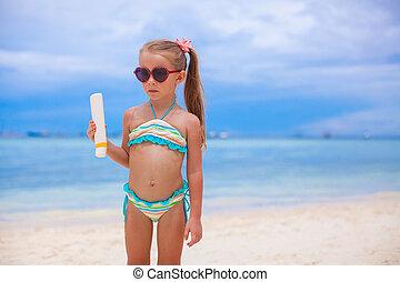 Little adorable girl in swimsuit holds suntan lotion bottle