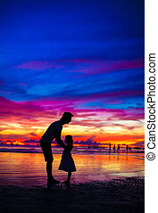 Father and daughter silhouettes in sunset at the beach on...