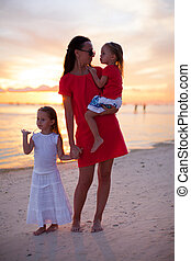 Mom and daughters silhouette in the sunset at the beach on Boracay