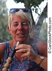 smoking a hookah water pipe - Lady smoking a hookah water...