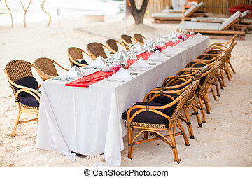 Summer empty open air table set for banquet on beach at...