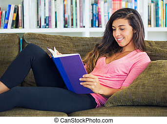 happy young woman reading a book - beautiful happy young...