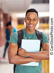 african american college student holding books - cheerful...