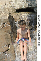 Quiet boy in waterfall