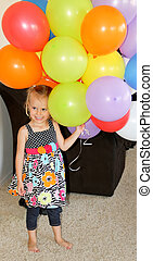 happy female toddler with balloons