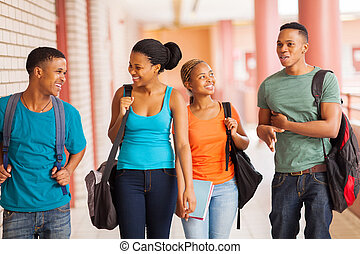 group of african college students walking in corridor -...