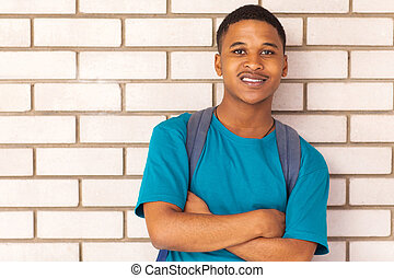 african american college boy leaning against a wall
