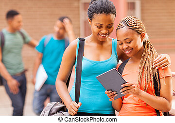 african college girl friends using tablet computer