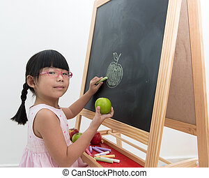 School time - Little Asian girl draws green apple on black...