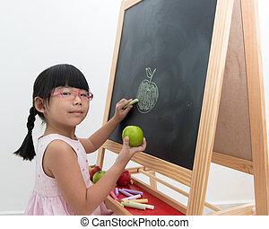 School time - Little Asian girl draws green apple on black...