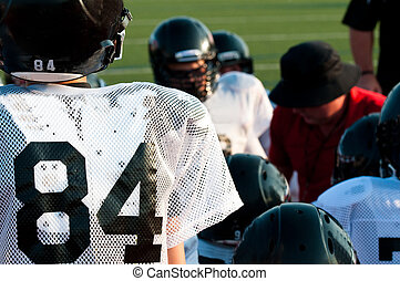 American football team in huddle - Young american football...
