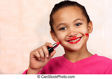 Lipstick girl - A smiling young girl applies lipstick in an...