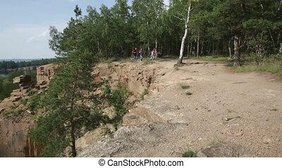 Trekkers - Trekking family running along the cliff edge,...