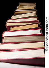 Stack of encyclopedia books over black background, photo...