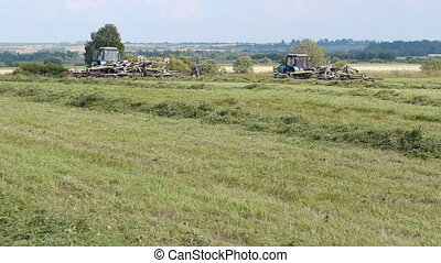 Harvest season - Agricultural machinery at work on farm land...