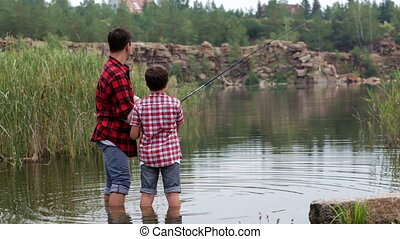 Fishermen - Dad and son having fun fishing in the lake