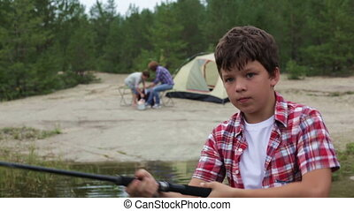 Learning to fish - Close-up of a serious boy learning how to...