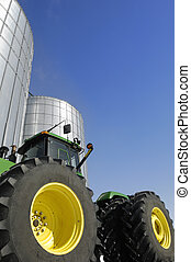 Tractor and grain silo - A large tractor in front of a...