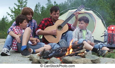 Camp song - Camping family gathering around dad who is...