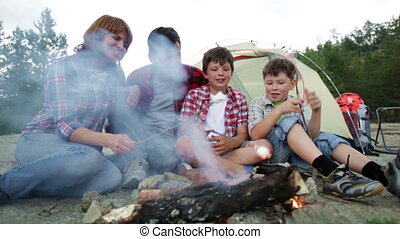 Marshmallows - Family of campers sitting by the fire and...