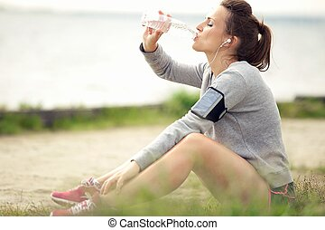 Female Jogger Resting and Drinking Bottled Water - Tired...