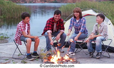 Camping bbq - Family sitting by the fire next to the tent...