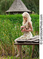 young girl sitting on a wooden bench by the lake