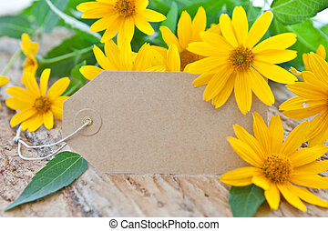 Blank paper tag and yellow coneflowers and leaves