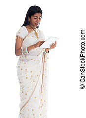 traditional indian woman in sari using tablet computer