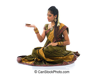 traditional indian woman with oil lamp during the celebration of deepawali or diwali on white background