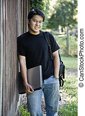 Happy asian student - A happy asian student carrying a...