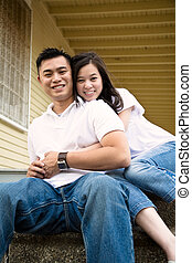 Happy asian couple - A happy asian couple sitting on the...