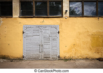 Old wooden gate in grungy yellow wall