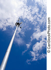 Floodlight - A single floodlight with blue sky and white...