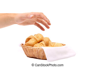 Hand reaches for the croissants in a basket.