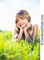 Pretty blonde woman admiring flowers while lying on...