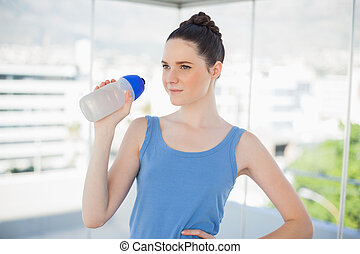 Pensive fit woman holding plastic flask after exercising in...