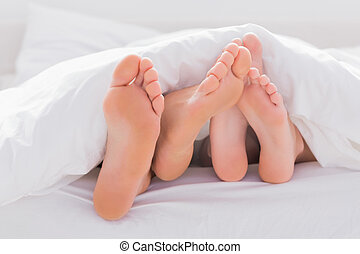 Couple rubbing their feet together under the duvet in bed