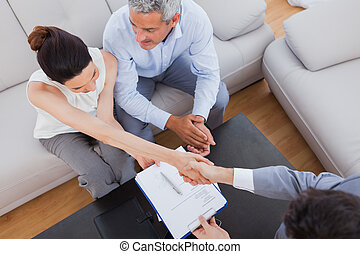 Businesswoman doing handshake with a businessman sitting on...